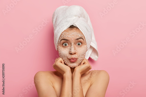 Obraz na plátně Horizontal shot of surprised Caucasian woman keeps palms under chin, looks with widely eyes, applies scrub mask, avoids problems with skin, stands shirtless against pink background