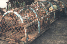 Close Up Of Wooden Lobster Pots Sat On The Harbour After Being Used In The Sea
