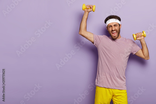 Foto Horizontal shot of motivated sportsman trains muscles, raises yellow dumbells, wears headband, casual outfit, being active, poses over purple studio wall, wants to have strong biceps