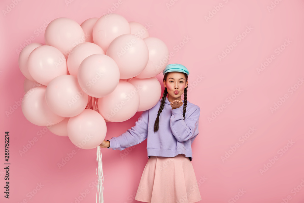Fototapety, obrazy: Beautiful dark haired lady with specific appearance, wears makeup, keeps lips rounded, blows air kiss at camera, has flirty expression, poses with helium balloons, isolated over pink background