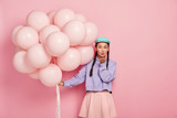 Beautiful dark haired lady with specific appearance, wears makeup, keeps lips rounded, blows air kiss at camera, has flirty expression, poses with helium balloons, isolated over pink background - 289752214