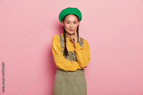 Valokuvatapetti Adorable satisfied woman with specific appearance, touches cheek with index finger, wears casual bright clothes, poses against pink wall, has makeup on face, thinks about plans