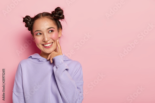 Obraz na plátně  Studio shot of glad lovely woman with smile, keeps index finger on cheek, looks