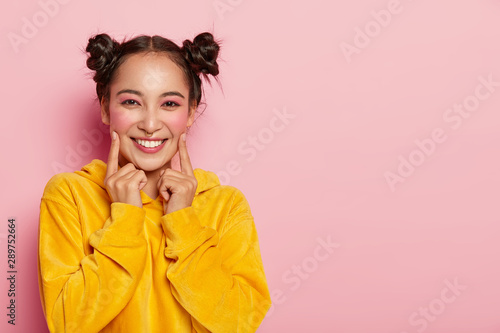 Obraz na plátně Photo of beautiful brunette woman with two buns, points index fingers on cheeks, dressed in casual corduoy yellow sweatshirt, wears bright pinup makeup, stands against rosy wall, free space