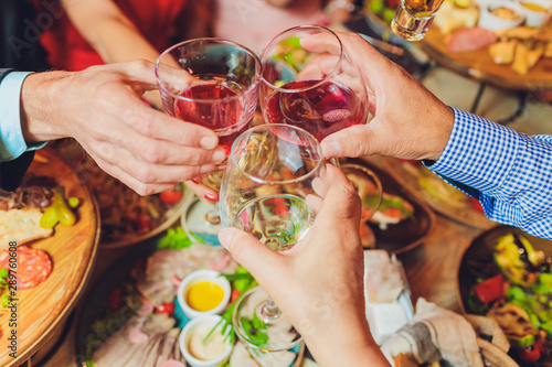 Photographie  Close up shot of group of people clinking glasses with wine or champagne in front of bokeh background