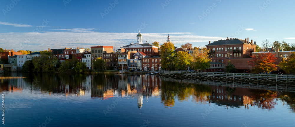 Fototapety, obrazy: The river front buildings of Exeter, New Hampshire are seen reflected in the water