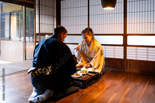 Photo Couple in kimono seiza sitting, holding chopsticks and eating food at traditiona