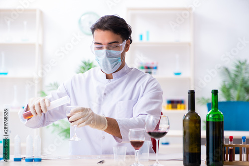 Stampa su Tela  Male chemist examining wine samples at lab