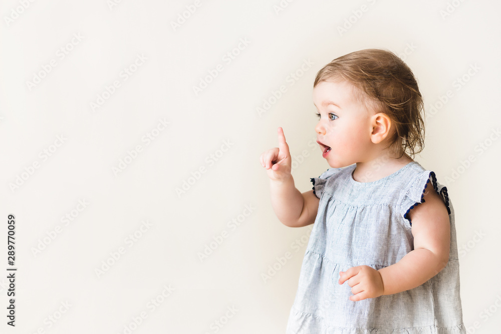Fototapety, obrazy: Baby girl pointing her finger, excited and emotional, on neutral background