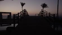 Slo Mo Tropical Sunrise Beachside Resort Tracking Over Bridge To Ocean Silhouette