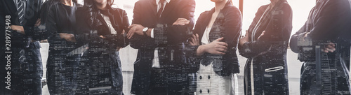 Obraz Business people group standing together with city office building background double exposure. Modern corporate job and human resources recruiting concept. - fototapety do salonu