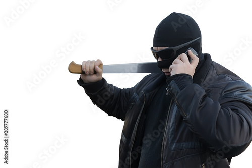 Fotografia bandit with a machete in a black mask talking on the phone on an white isolated