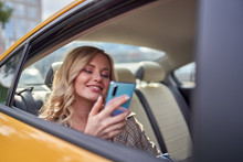 Photo Of Happy Blonde With Phone In Her Hand Sitting In Back Seat In Yellow Taxi