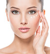 Leinwandbild Motiv woman with healthy face applying cosmetic cream under the eyes