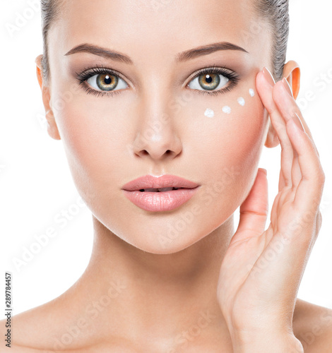 Canvastavla  woman with healthy face applying cosmetic cream under the eyes