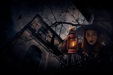 Halloween Witch Holding Ancient Lamp Standing Over Grunge Castle, Dead Tree, Bird Fly, Full Moon And Cloudy Spooky Sky, Halloween Mystery Concept