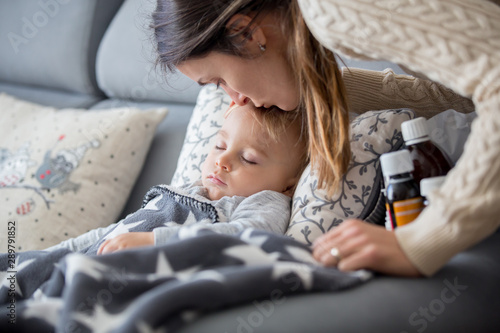 Fotografia  Sick child, toddler boy lying in bed with a fever, resting at home