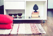 Cozy Home Interior Decor, Burning Spa Aroma Candles In Coconut Shell, Metal Vase, Pile Of Books, On White Glass Nightstand Near A Multi-colored Rug With Decorative Pillows Background.