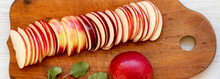 Slices Of Fresh Red Apples On Wooden Board Over White Wooden Background, Top View. Flat Lay, Overhead, From Above. Close-up.