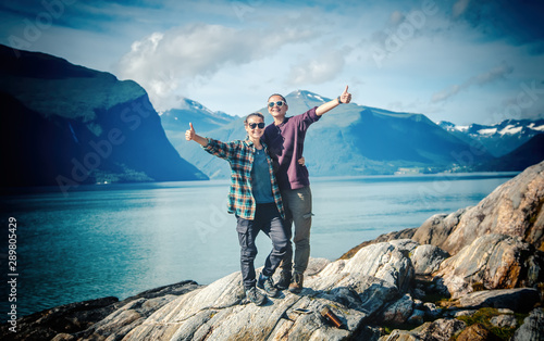 Two young happy women girlfriends couple travel together in norway, stand on the Wallpaper Mural