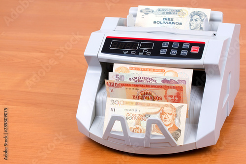 Obraz na plátně  Bolivian Boliviano in a counting machine