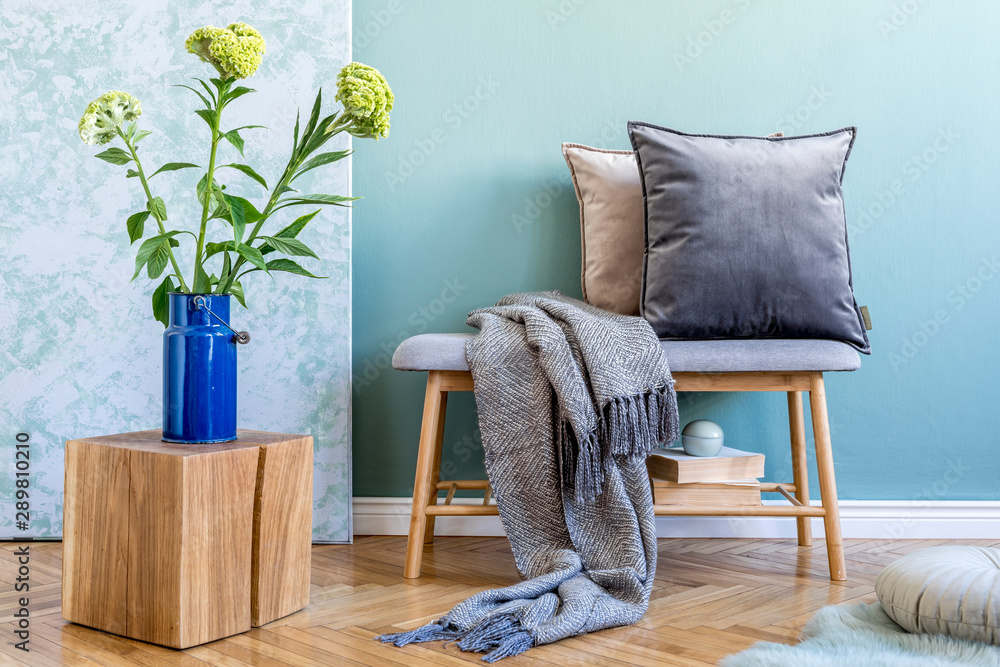 Fototapeta Stylish scandinavian interior of living room with wooden bench, colorful pillows, plaid, wooden cube, flowers in vase, books and elegant personal accessories. Interior design and modern home decor.