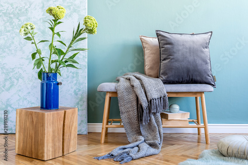 Stylish scandinavian interior of living room with wooden bench, colorful pillows, plaid, wooden cube, flowers in vase, books and elegant personal accessories Canvas Print