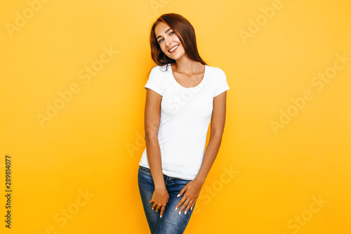 Young beautiful woman in a white t-shirt posing on a yellow background Wallpaper Mural