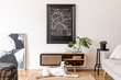 Design scandi home interior of living room with wooden commode, gray sofa, black rattan pouf, plant and elegant accessories. Stylish home decor. Mock up design map project. Dog is lying on the carpet