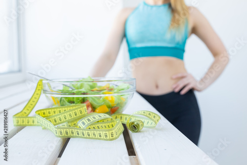 Foto Healthy lifestyle, fitness and diet concept - close-up dietary salad andmeasurin