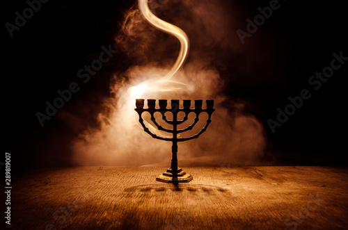Fotografie, Obraz Low key image of jewish holiday Hanukkah background with menorah on dark toned f