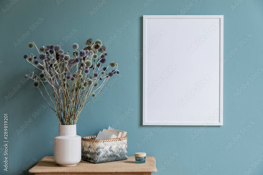 Fototapety, obrazy: Stylish and minimalistic composition of sitting room with white mock up frame, wooden shelf, flowers in vase , basket and elegant accessories. Design home decor. Template. Eucalyptus color concept.