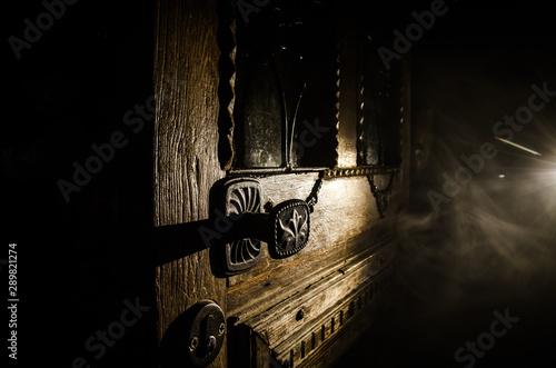 Close up view of old antique wooden door inside dark room. Selective focus
