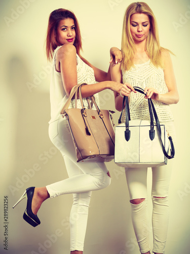 Fototapeta  Two women in white clothes with bags handbags.
