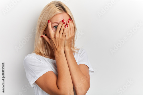 Fotografía young fair-haired girl covering face with hands, her eyes full of terror and pan
