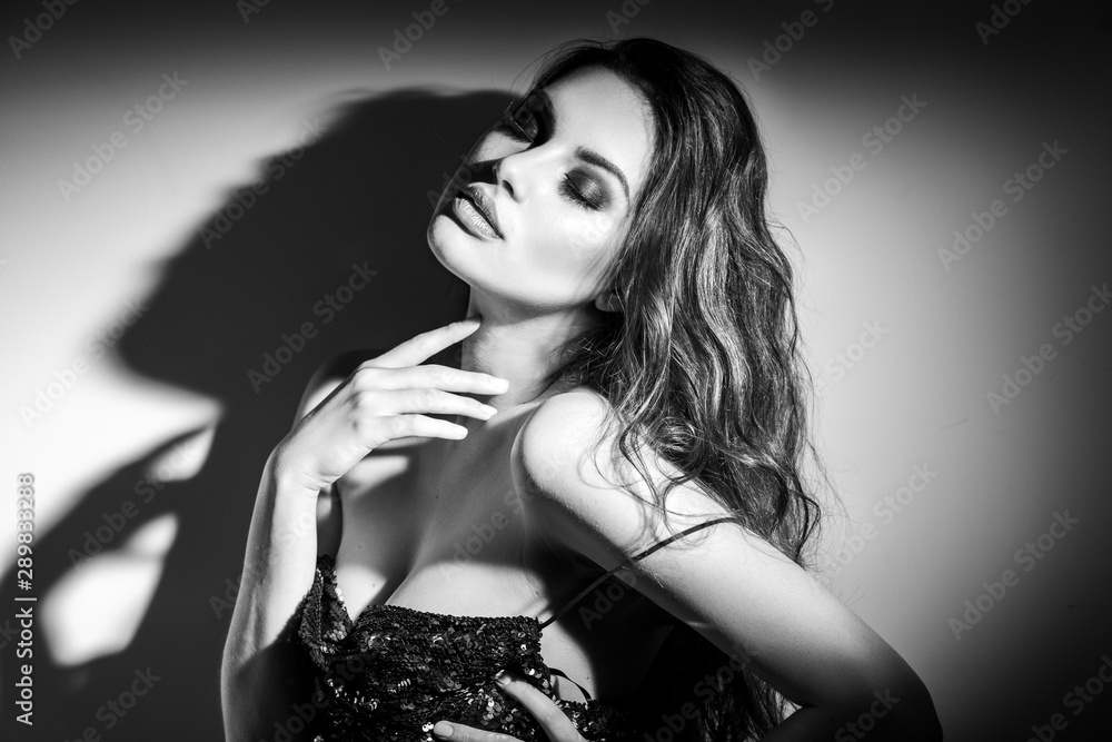 Fototapeta Sexy Young Woman black and white portrait. Seductive young woman in lingerie in darkness. Glamour lady with long hair posing in spotlight. Gorgeous seductive model girl with long hair b&w
