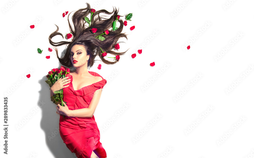 Fototapeta Beauty Sexy Model girl lying on white background with red rose flowers in her hair and a bunch. Beautiful young woman with long hair and perfect make-up, red seductive lips, smoky eyes. Birthday Gift