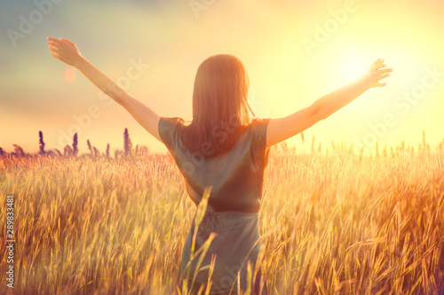 Happy autumn woman raising hands over sunset sky, enjoying life and nature. Beauty female on field looking on sun. Silhouette of girl in sunlight rays. Fresh air, environment concept. Dream of flying
