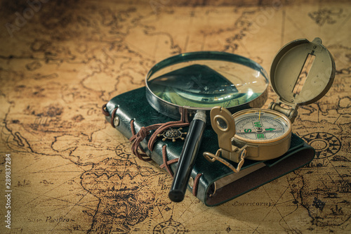 Obraz old map with compass, notebook and magnifying glass. The concept of searching for interesting places or treasures around the world. - fototapety do salonu
