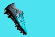 Football Boots Hovering In The Air, As If Hitting The Ball, Concept, Sports Shoes, On A Turquoise Background