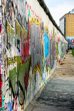 Part Of The Berlin Wall Full Of Graffiti And Taken From A Very Lateral Angle At The East Side Gallery