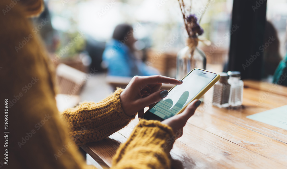 Fototapeta girl hold in hand empty screen mobile phone, person type message on smartphone in cafe, relax tourist travels plan trip, hipster enjoy journey in cityscape, lifestyle holiday concept, internet online