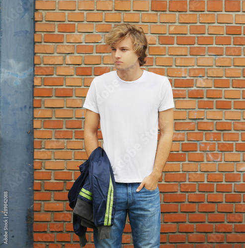 Obraz na plátně  Teenager standing near a brick wall