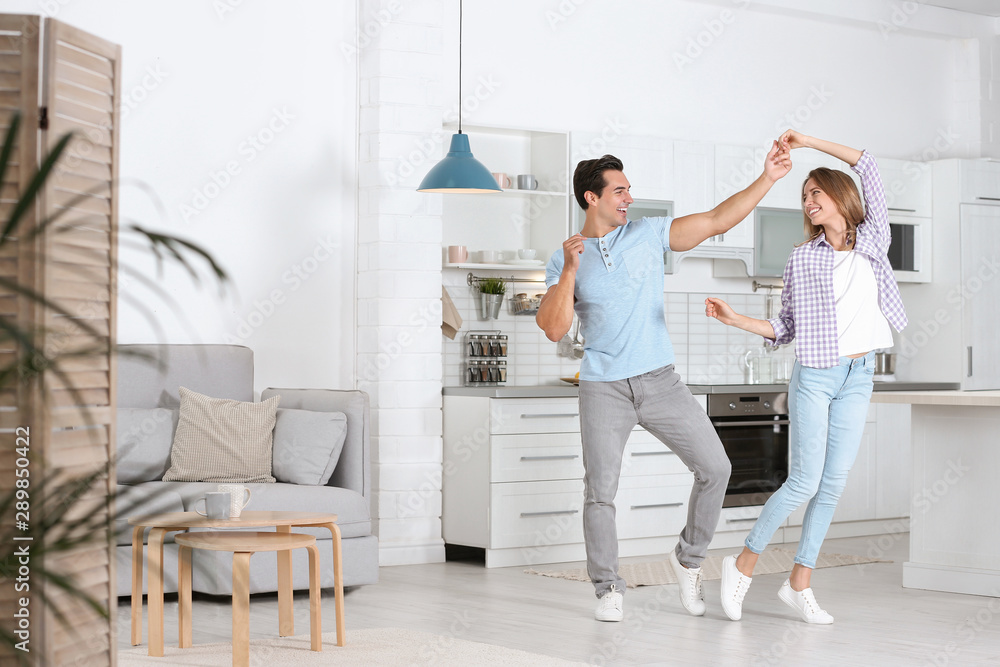 Fototapety, obrazy: Beautiful young couple dancing in kitchen at home