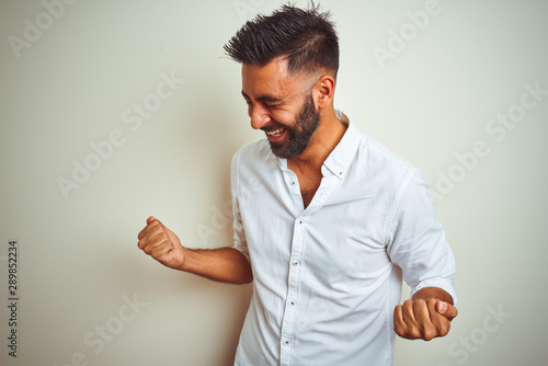 Young indian man wearing elegant shirt standing over isolated white background very happy and excited doing winner gesture with arms raised, smiling and screaming for success Canvas Print