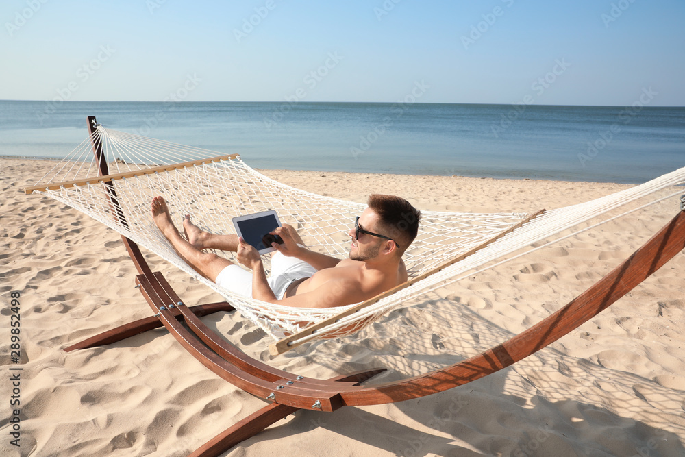 Fototapeta Young man with tablet in hammock on beach