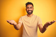 canvas print picture - Young indian man wearing t-shirt standing over isolated yellow background smiling cheerful offering hands giving assistance and acceptance.