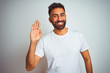 canvas print picture - Young indian man wearing t-shirt standing over isolated white background Waiving saying hello happy and smiling, friendly welcome gesture