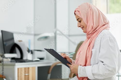 Fotografiet  Side view portrait of Middle-Eastern woman wearing hijab working as nurse in med