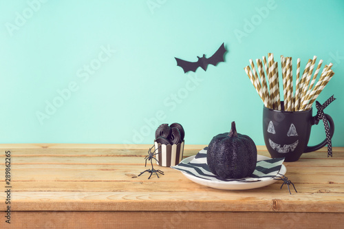 Foto  Halloween holiday table setting with glitter black pumpkin, party chalkboard cup